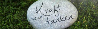 Stein mit der Aufschrift: Neue Kraft tanken