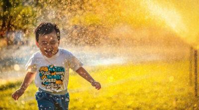 Junge spielt in einer Wasserfontäne